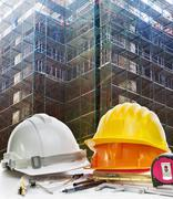 safety helmet and engineering working tool against building construction mesh - stock photo
