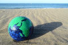 Globe earth on the beach Stock Photos