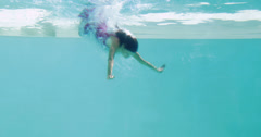 Brunette in evening gown diving into swimming pool Stock Footage