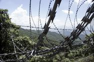 Stock Photo of Barbed wire in front of beautiful nature