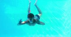 Man in snorkel jumping in swimming pool waving at camera Stock Footage
