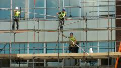 Construction workers on scaffolding repairing a building Stock Footage