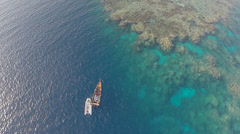 Aerial shot of small fishing boat in coral reef - TWO CLIP IN ONE! Stock Footage