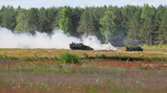 Military vehicles drive in the field, smoke Stock Footage