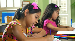Two cute little girls doing homework smile at camera Stock Footage