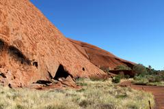 Ayes Rock and tourists in Australia - stock photo