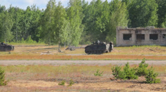Infantry vehicles drive in the field near forest and destroyed building Stock Footage