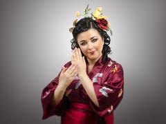 Stock Photo of flowers haired kimono woman showing traditional gestures