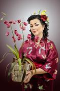 Stock Photo of kimono caucasian woman holding an orchid