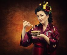 Stock Photo of flowers haired kimono woman eating with chopsticks