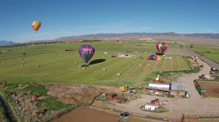 Aerial hot air balloons landing rural farm field HD 061 Stock Footage