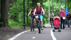 People Ride And Walk by Bicycle Path in Summer City Park. Stock Footage