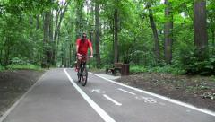 People Ride by Bicycle Path in Summer City Park. Stock Footage