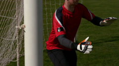 Goalkeeper in red saving a goal during a game Stock Footage