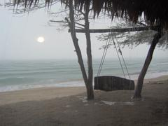 Stock Photo of Rainy seaside swing with dim sun in Asia
