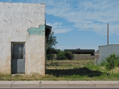 Dilapidated white adobe stucco building with train in background Stock Photos