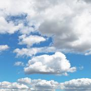 Fluffy clouds in blue afternoon sky Stock Photos