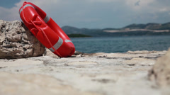 A red rescue buoy near a beach - stock footage