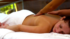 Peaceful woman enjoying a back massage at the spa - stock footage