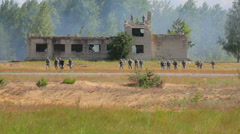 American soldiers run in the field with old destroyed building in a background Stock Footage