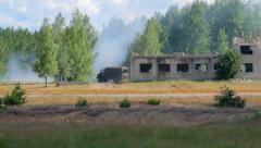 Military vehicles drive in the field near forest and destroyed building Stock Footage