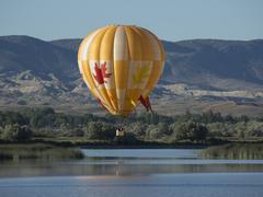 Yellow hot air balloon over valley lake - stock photo