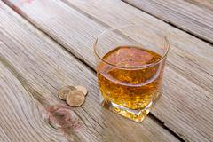 Tumbler of whiskey and tip on a bar counter Stock Photos