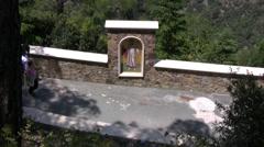 People walking along path with fresco near Kykkos monastery Stock Footage