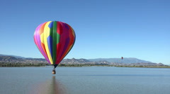Hot air balloon skips across mountain valley lake HD 064 Stock Footage