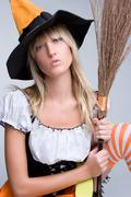 Witch holding broom Stock Photos