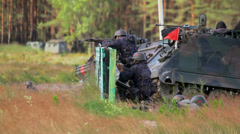Group of soldiers shooting in the field near an armoured vehicle - stock footage