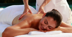 Happy brunette enjoying a massage poolside Stock Footage