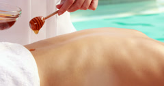 Beauty therapist pouring honey onto womans back Stock Footage