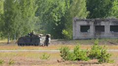 Soldiers drive backwards in an armoured vehicle in the field Stock Footage
