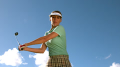 Lady golfer swinging her club - stock footage