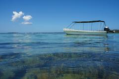 Boat anchored near a shallow coral reef Stock Photos