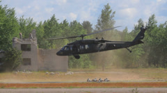 Military helicopter Black Hawk take off, soldiers lying down in the field Stock Footage