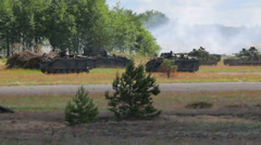 Many armoured vehicles with soldiers drive in the field near the forest, attack Stock Footage