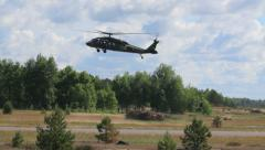 Military helicopter flies above the field, lands, Black Hawk Stock Footage