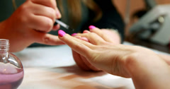 Nail technician painting top coat onto customers pink nails Stock Footage