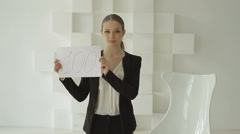 Young beautiful businesswoman showing number 100 on sheet of paper. Stock Footage