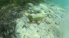 Glass bottles and other trash underwater in tide mark Stock Footage