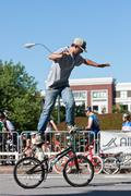 man practices flatland bike tricks before bmx competition - stock photo