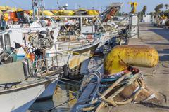 Fishing boats in harbor - yellow rusty bollard Stock Photos