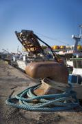 Fishing boats in harbor - bollard with blue rope Stock Photos