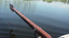On dark lake water surface dripping small drops from paddle Stock Footage