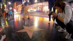 People crowd taking pictures at Michael Jackson star on Hollywood Walk of Fame Stock Footage