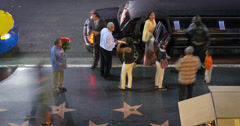 People party loading into black stretch limo taxi cab on Hollywood Walk of Fame. Stock Footage