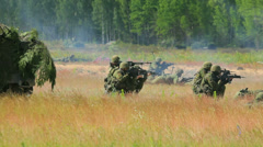 Soldiers shoot in the field near the forest, armored vehicle, camouflage Stock Footage