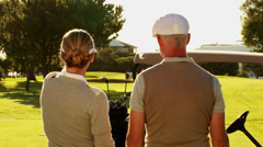 Couple standing on the golf course looking around - stock footage